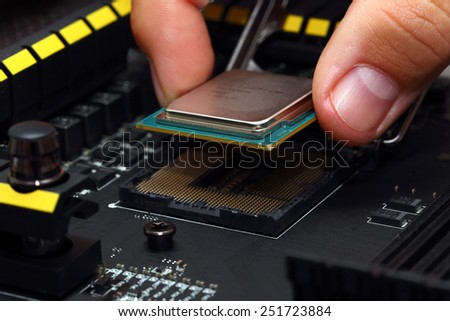 Installing modern central processor unit into motherboard - stock photo