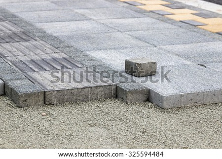 Installing pedestrian path with paver bricks. Sidewalk pavement. Shallow dof. - stock photo