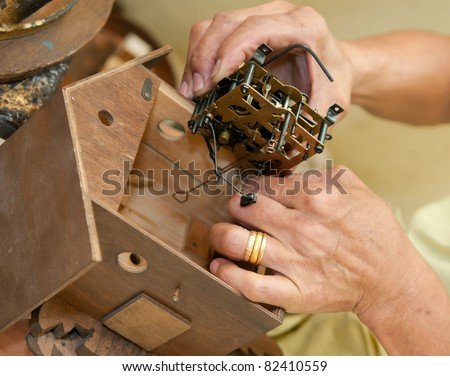 Installing the primary mechanism block in the interior of a cuckoo clock - stock photo