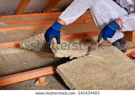 Installing thermal insulation layer - closeup on hands cutting rock wool