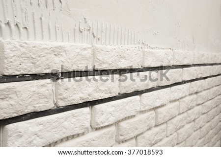 Installing white decorative bricks on the wall
