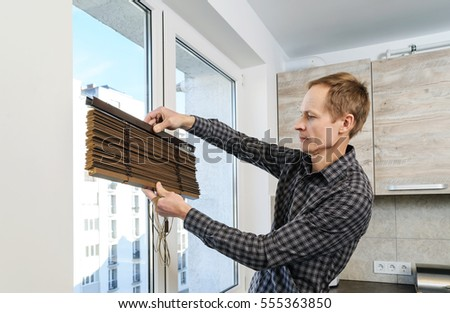 Installing wooden blinds. A man holds the folded jalousie.
