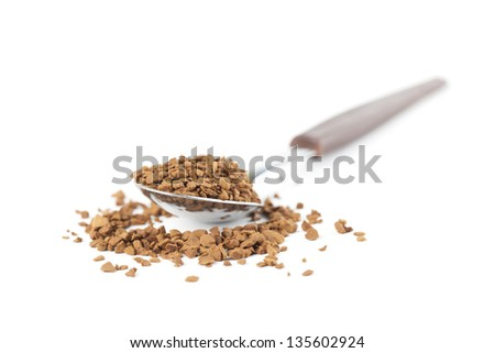 Instant coffee granules in a spoon isolated on white background