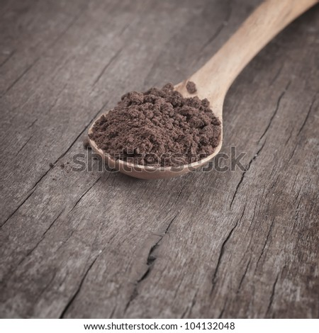 Instant coffee in the spoon on wooden table - stock photo