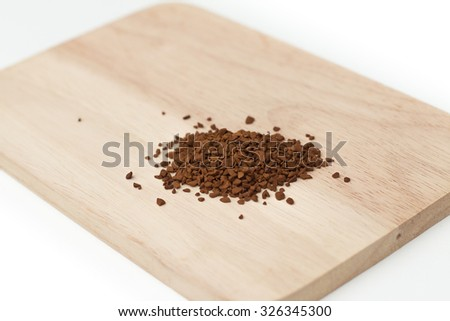 Instant coffee powder on wood plate and isolated on white background - stock photo