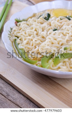 instant noodle and chopstick with wood background. Selective focus,shallow depth of field.Vibrant Colors