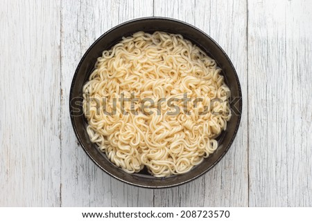 Instant noodles in Black dish on wood background - stock photo