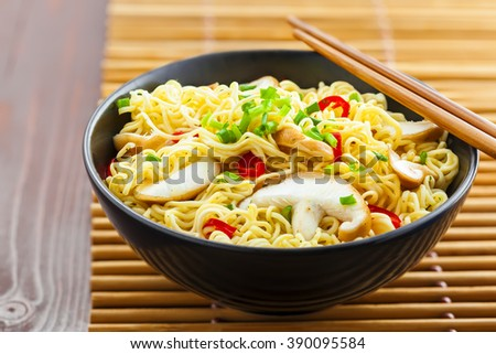 Instant noodles with shiitake mushrooms, pepper and onion in a bowl, Asian food on a table