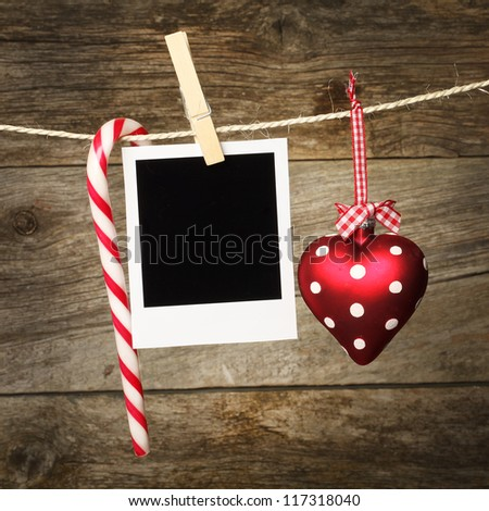 Instant photo frame on the wooden texture with christmas decoration - stock photo