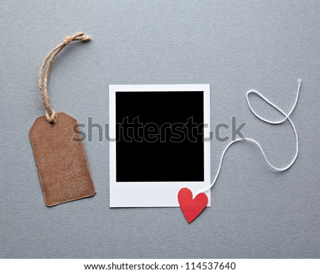 Instant photo frame with blank gift tag and small red heart. On gray paper background. - stock photo