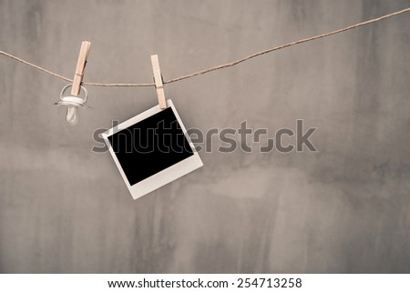 Instant photo frames and pacifier hanging on the clothesline - stock photo