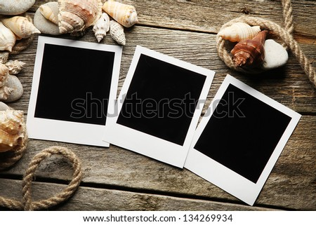 Instant photo frames on the wooden texture with seashells around - stock photo
