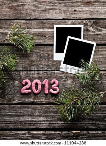 Instant photo frames with numbers 2013 and spruce branches on grunge wood background. - stock photo