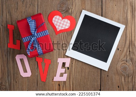 Instant photo with gift and paper hearts on old wooden background - stock photo