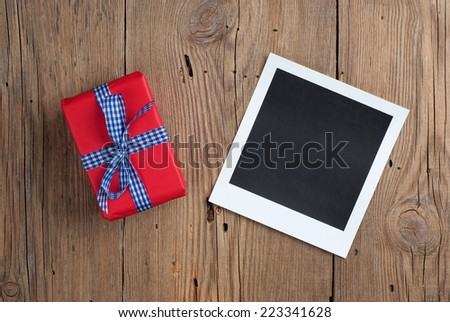 Instant photo with gift on old wooden background - stock photo