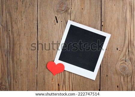 Instant photo with paper hearts on old wooden background - stock photo