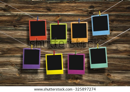 Instant photos in polaroid style hanging on two clotheslines  - stock photo