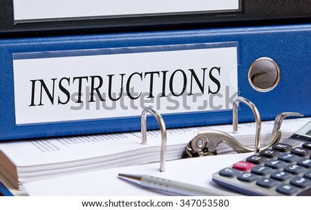 Instructions - blue binder on desk in the office with calculator and pen - stock photo