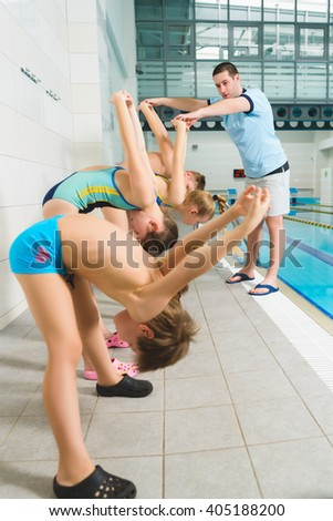 Instructor  and group of children doing exercises near a swimming pool - stock photo