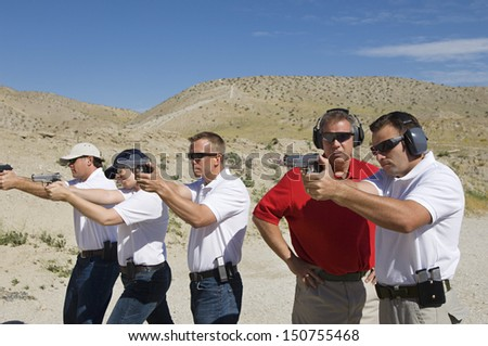 Instructor assisting men aiming hand guns at firing range - stock photo