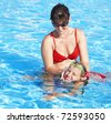 Instructor girl learn child swim in swimming pool. - stock photo