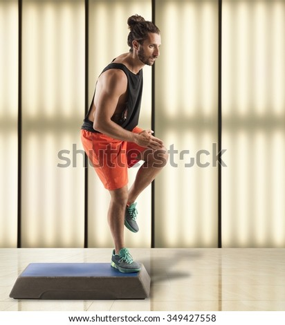 Instructor man does fitness with a step