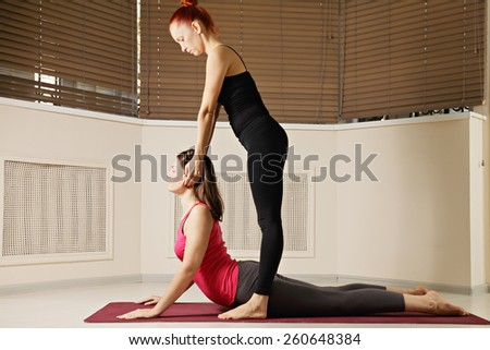 Instructor stretches students neck at yoga exercise - stock photo