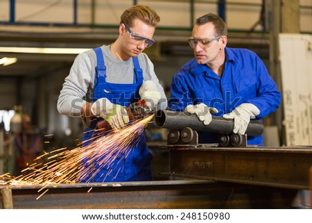 instructor teaches steel construction trainee how to use an angle grinder - stock photo