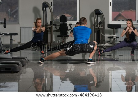 Instructor With Fitness Class Performing Step Aerobics Exercise In Gym