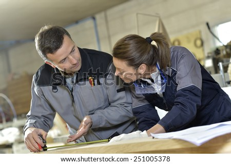 Instructor with trainee in carpentry workshop - stock photo