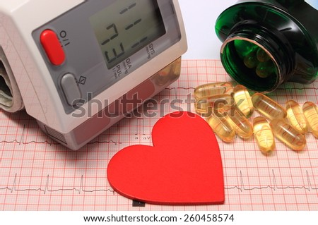 Instrument for measuring blood pressure, red heart shape and tablets on electrocardiogram graph, ekg heart rhythm, medicine concept - stock photo
