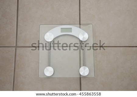 Instrument for measuring pounds or kilograms /Digital WeightDevice/Glass scale on tile surface - stock photo