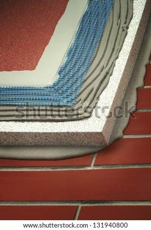 insulated brick wall with plaster, glue, net, polystyrene, thermal protection - stock photo