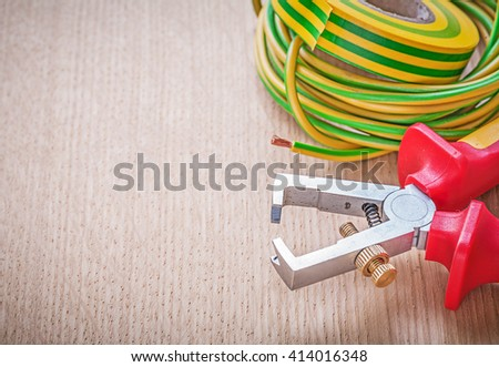 Insulating tape electric cable wire stripper pliers on wooden board electricity concept. - stock photo