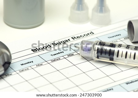 Insulin pen with blood sugar record and diabetic supplies. - stock photo