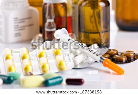 insulin syringe and different medicament in on white and  blurred bottles and ampules  background - stock photo