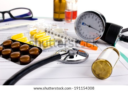 insulin syringe, different medicaments, doctor's stethoscope and glasses on medical form on white background - stock photo