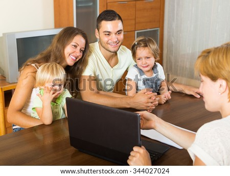 Insurance agent consulting happy young family with kids at home. Focus on woman - stock photo