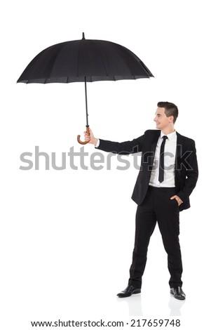 Insurance agent holding open umbrella. Full length studio shot isolated on white. - stock photo