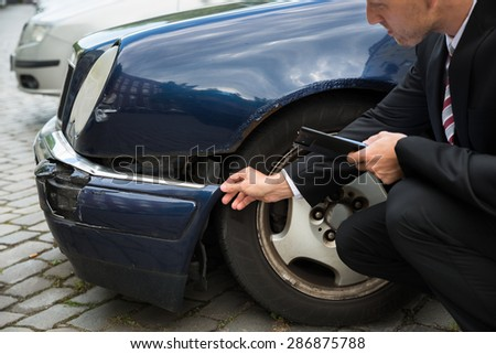 Insurance Agent Inspecting Car Involved In Accident