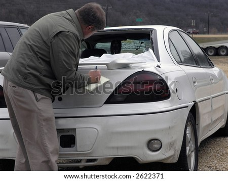 Insurance agent looks at vehicle for claim resolution - stock photo