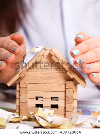 Insurance agent protecting house with his hands