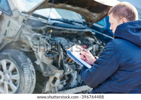 Insurance agent recording car damage on claim form - stock photo