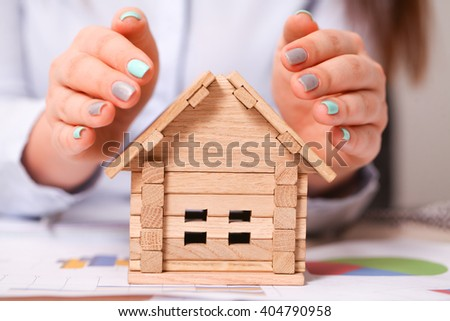 Insurance and house protection concept. Beautiful house under woman's hands