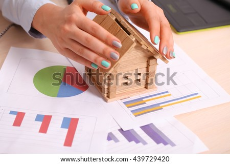 Insurance and house protection concept. Beautiful house under woman's hands - stock photo