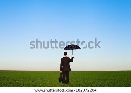 insurance concept, businessman in the field - stock photo