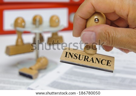 insurance marked on rubber stamp in hand