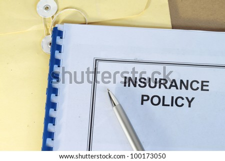 insurance policy folder on desk in office with pen and manila envelop - stock photo