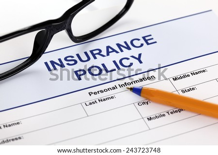 Insurance policy form with glasses and ballpoint pen. - stock photo