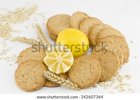 Integral biscuits and decorated lemon on white background with wheat and seeds spread all around - stock photo